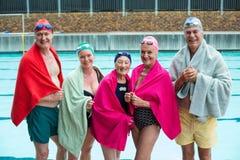 Glückliche ältere Schwimmer bedeckt in den Tüchern am Poolside Stockfotografie