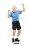 Glückliche ältere Stellung auf einer Gewichtsskala Lizenzfreie Stockbilder