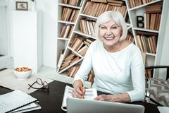 Glückliche ältere weibliche Person, die ihr Lächeln demonstriert stockfoto