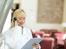 Glückliche Ärztin, die mit einem Patienten an einem Telefon spricht stockfotos