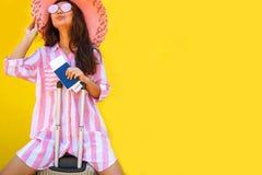 Glückliche überglückliche junge Frau im rosa haltenen Koffer, Passbordkartekarte lokalisiert auf gelbem Hintergrund stockfoto