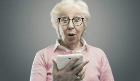 Glückliche überraschte ältere Dame unter Verwendung einer Tablette lizenzfreies stockfoto
