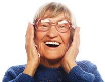 Glückliche überraschte ältere Frau, die Kamera betrachtet Stockfotografie