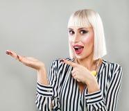 Glückliche überraschte Frau, die leeren Kopien-Raum auf der offenen Hand zeigt Lizenzfreie Stockfotos