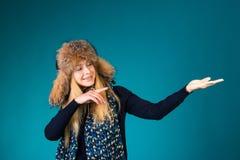 Glückliche überraschte Winterfrau, die das Zeigen auf leeres copyspace zeigt stockbilder