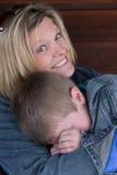 Glückliche aber frustrierte Mutter hält sie untröstlich Stockbild