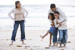 Glückliche African-Americanfamilie, die auf Strand lacht Stockfoto