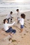 Glückliche African-Americanfamilie, die auf Strand spielt Stockfotos