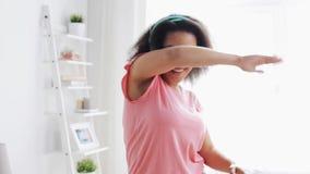 Glückliche afrikanische Frau in den Kopfhörern, die zu Hause tanzen stock footage