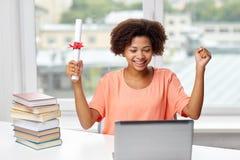 Glückliche afrikanische Frau mit Laptop, Büchern und Diplom Lizenzfreie Stockfotos