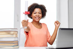Glückliche afrikanische Frau mit Laptop, Büchern und Diplom Stockbild