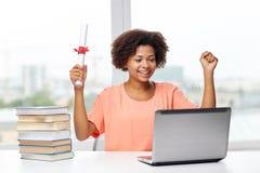 Glückliche afrikanische Frau mit Laptop, Büchern und Diplom Stockfotos
