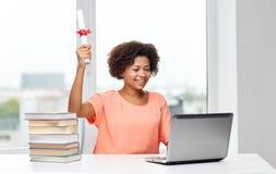 Glückliche afrikanische Frau mit Laptop, Büchern und Diplom Lizenzfreie Stockfotografie