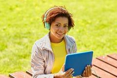 Glückliche afrikanische Frau mit Tabletten-PC und -kopfhörern Lizenzfreies Stockbild