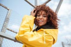 Glückliche afrikanische gelockte junge Dame, die gelben Mantel trägt lizenzfreie stockbilder