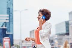 Glückliche afrikanische Geschäftsfrau, die um Smartphone ersucht Stockfoto