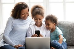 Glückliche Afroamerikanerfamilie unter Verwendung der tragbaren Geräte zusammen stockfotos
