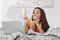 glückliche Afroamerikanerfrau, die das Eeinkaufen im Bett macht stockbilder
