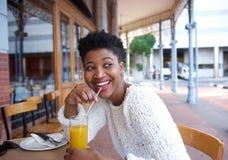 Glückliche Afroamerikanerfrau, die Orangensaft trinkt lizenzfreie stockfotografie