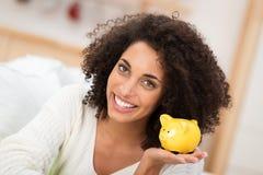 Glückliche Afroamerikanerfrau mit einem Sparschwein Stockbilder