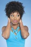 Glückliche Afroamerikanerfrauen-Bedeckungsohren vorbei beim Schauen des weg farbigen Hintergrundes Stockbild
