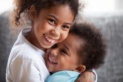 Glückliche Afroamerikanergeschwisterumfassung, zusammen sitzend stockfotografie