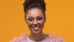 Glückliche afroe-amerikanisch Dame in den modernen Brillen lächelnd in Kamera, städtische Art stock footage