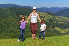 Glückliche aktive Familie auf Sommerferien im Berg Stockfotografie