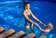 Glückliche aktive Mutter und Tochter beim Swimmingpoolspielen Lizenzfreie Stockfotografie