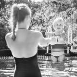 Glückliche aktive Mutter und Tochter beim Swimmingpoolspielen Stockbilder