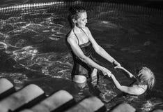 Glückliche aktive Mutter und Tochter beim Swimmingpoolspielen Stockfoto