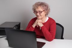 Glückliche alte Dame, die auf einem Laptop spricht Moderne Großmutter stockfotos