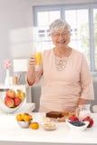 Glückliche alte Dame, die Orangensaft trinkt Stockfotos
