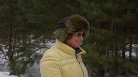 Glückliche alte Frau des Porträts, die in den Winterwald geht in Winterwochenende geht stock video