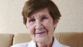 Glückliche alte Frau, die an der Kamera lächelt stock video footage