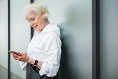 Glückliche alte Frau, die ihr nahe gelegenes Stadtgebäude des Smartphone verwendet Lizenzfreie Stockbilder