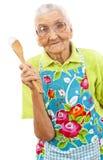 Glückliche alte Frau mit hölzernem Löffel Lizenzfreie Stockbilder