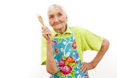 Glückliche alte Frau mit hölzernem Löffel Stockfotografie