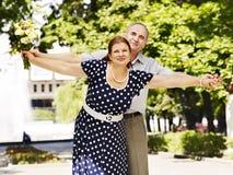 Glückliche alte Paare mit Blume. Lizenzfreies Stockbild