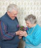 Glückliche alte Paare riechen Blumen Stockbild