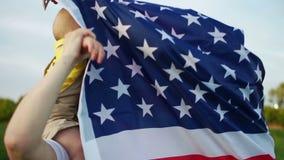 Glückliche amerikanische Familie auf einem Picknick am 4. Juli Gro?v?terliche Spiele mit Enkel Das Baby sitzt auf den Mutterschul stock video