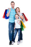 Glückliche amerikanische Familie mit dem Kind, das Einkaufstaschen hält Stockfoto