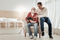 Glückliche angenehme Mannsitzen- und -säentablette lizenzfreie stockfotos