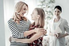 Glückliche angenehme Mutter, die ihre Tochter lächelt und umarmt Stockfotos