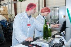 Glückliche Angestellte, die Maschine verwenden, um Wein an der Fabrik abzufüllen Lizenzfreies Stockfoto
