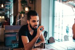 Glückliche arabische junge Männer, die im Dachbodencafé hängen Freunde, die am Fenster im Lounge Bar Tee trinkend sprechen lizenzfreies stockfoto
