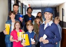 Glückliche Arbeitskraft mit Familien im Hintergrund am Kino Lizenzfreie Stockbilder