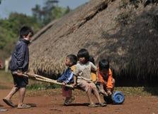 Glückliche Armelächelnkinder in traditionellem Dorf Asiens Stockfotos