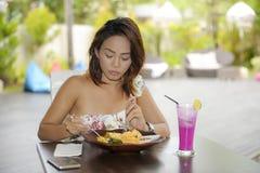 Glückliche Asiatin auf ihrem 20s gesundes Lebensmittel für das Brunchfrühstück oder -mittagessen genießend, die an der Kaffeestub Lizenzfreie Stockfotografie