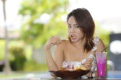 Glückliche Asiatin auf ihrem 20s gesundes Lebensmittel für das Brunchfrühstück oder -mittagessen genießend, die an der Kaffeestub Stockfotografie